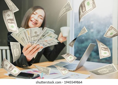 Successful beautiful business young woman holding money US dollar bills in hand on office desk, business concept