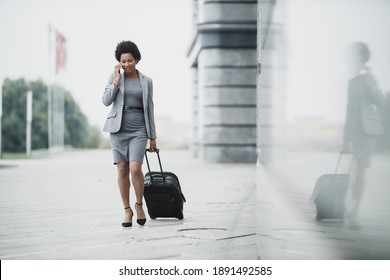 A successful black business woman walking with her luggage and using smart phone outside of the airport.