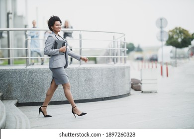 A successful black business woman while walking down a stairs in front a corporate building.