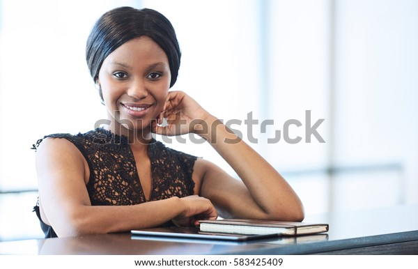 Successful black businesswoman looking into camera while seated at counter with bright backlighting from large windows behind her, and her notebook and electronic tablet in front of her.