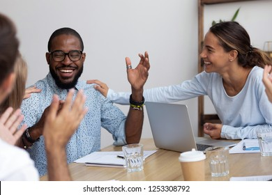 Successful black company member got promotion or monetary reward feels happy and proud colleagues congratulate him applauding laughing together. Diverse business people celebrating business success