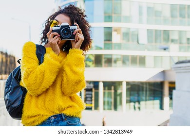 Successful  black female photographer making photos on modern architecture background. Wearing back pack, yellow sweater and glasses.