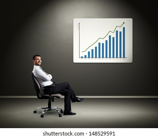 successful boss sitting on chair against board with diagram