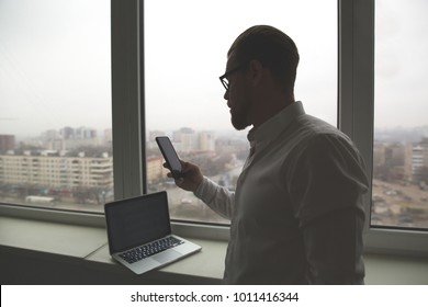 Successful brutal man with glasses standing at the window solving the business issues on the phone