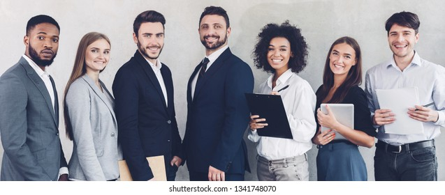 Successful business colleagues looking at camera, having break in office, grey background