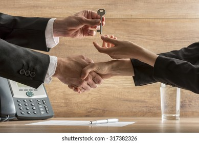 Successful business deal - real estate agent and new female homeowner exchanging house key while shaking hands over a contract of house sale.