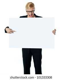 Successful business female pointing at white blank billboard. Looking down