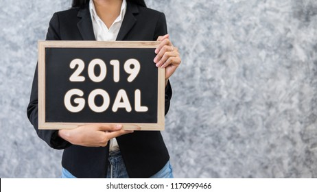 Successful business goal in new year 2019.Business goal 2019.Happy new year celebration.Woman holding blackboard label with 2019 goal text.
