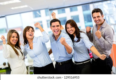 Successful business group with arms up at the office