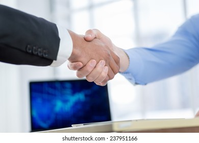 Successful business handshake. Close-up view of a handshake while two successful businessman shaking hands at the table against each in the business office in formal wear and work at a laptop.