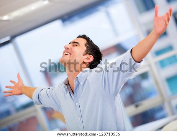 Exitoso hombre de negocios celebra con los brazos abiertos