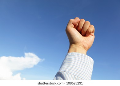 Successful business man hand fist gesture close up in the air with blue sky and white cloud