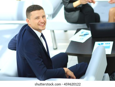Successful business man  with his staff in background at office