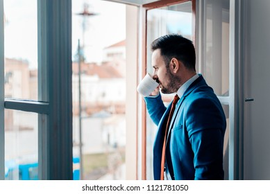 Successful business man looking at city through open window while drinking from a cup.