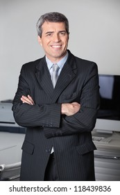 Successful business man smiling with his arms crossed