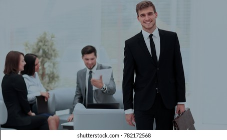 Successful business man standing with his staff in background at