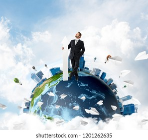 Successful business man in suit holding huge white arrow in hand while standing on Earth globe with cloudy skyscape view on background. Elements of this image are furnished by NASA