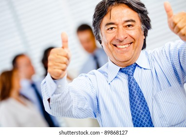 Successful business man with thumbs-up at the office