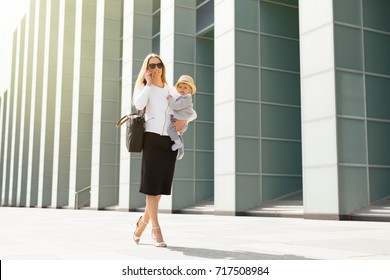 Successful business mother in city with baby in her hands