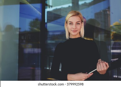 Successful business owner posing with touch pad while standing outside near glass entrance door of office building,confident woman entrepreneur holding digital tablet and look at the camera with smile