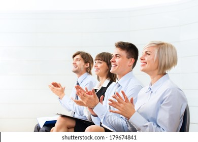 Successful business people group applauding after presentation, businesspeople applause sitting in row at the meeting office room on conference