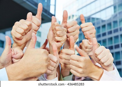 Successful business people holding many thumbs up