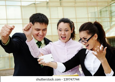 Successful business people screaming and looking at mobile phone
