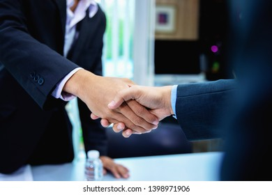 Successful business people shaking hands after closing a deal