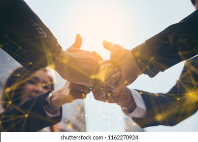 Successful business people showing thumbs up sign.Business people shaking hands, finishing up a meeting.Businesspeople having meeting in city.block chain Technology concept.