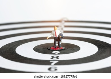 Successful business people standing with arrow hit on target, selective focus miniature business man congratulate on all the achievements in their career.