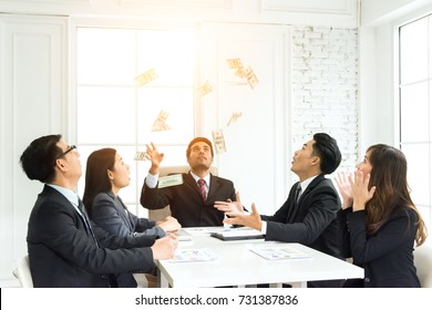 Successful business people throwing money banknotes flying in the air with business team in the office. Happy achievement business manager giving bonus to business team during the meeting.