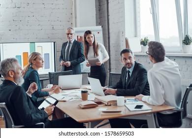 Professionnels des affaires ayant réussi à présenter un rapport analytique tout en travaillant avec des collègues du bureau moderne