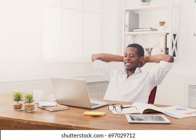 Successful business. Relaxed black businessman in casual with laptop in modern white office interior. Lifestyle portrait