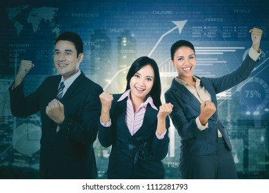 Successful business team celebrating their triumph by lifting hands while standing with growth finance graph background