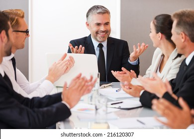 Successful business team. Confident mature man in formalwear smiling and gesturing while his colleagues applauding to him