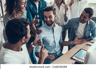 Successful Business Team Congratulating Colleague. Group of Young Happy Collegues Celebrating in Modern Office. Creative Successful Team at Work. Teamwork Concept. Corporate Lifestyle