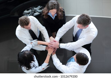 Successful business team with folded their hands together