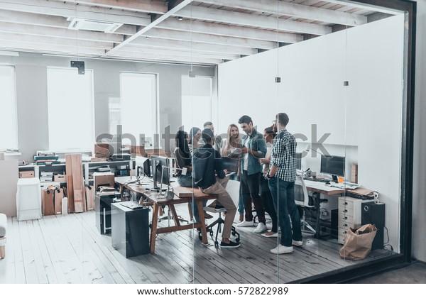 Erfolgreiches Geschäftsteam. Volllange junge moderne Menschen in intelligentem, lockuellem Kleiderbezug mit einem Treffen hinter der Glaswand im Kreativbüro