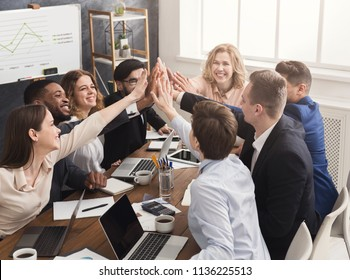 Successful business team is giving group high five and smiling, celebrating successful teamwork at meeting, copy space