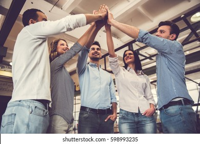 Successful business team is giving high five and smiling while standing in office