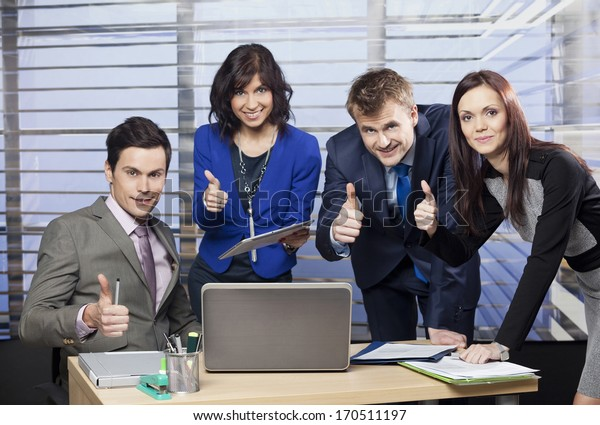 Successful business team giving thumbs up