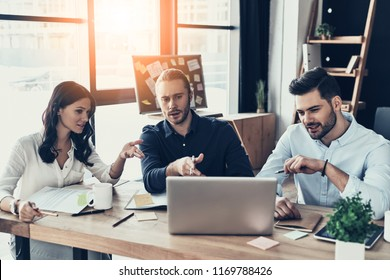 Successful business team. Group of young modern people in smart casual wear pointing at laptop while sitting in the creative office