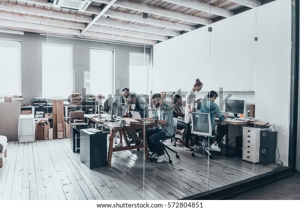Erfolgreiches Geschäftsteam.  Gruppe junger Unternehmer, die zusammen arbeiten und kommunizieren, während sie an ihren Arbeitsplätzen im Büro sitzen