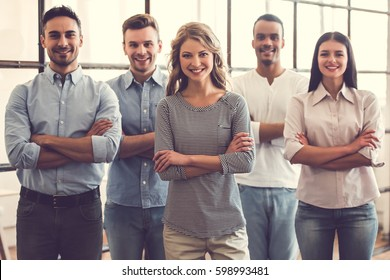 Successful business team is looking at camera and smiling while standing with crossed arms in office