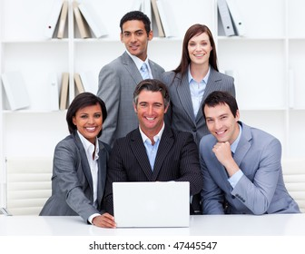 Successful business team looking at a laptop in the office