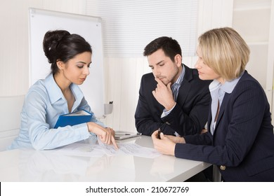 Successful business team sitting at the table in the office.  Male and female people wearing blue clothes.