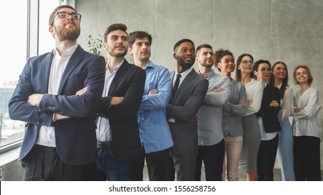 Successful business team standing in row with crossed arms and headed with boss, looking aside in office