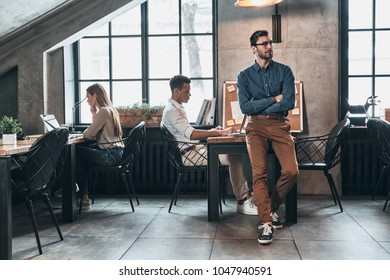 Successful business team. Young modern people in smart casual wear concentrating at work while spending time in the office