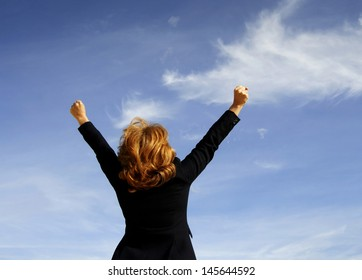 Successful business woman with arms up and blue sky background