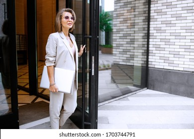 Successful business woman in cityscape background. Stylish lady outdoor with laptop. Fahionable female manager leaves her modern office. Street fashion.